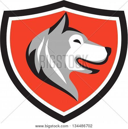 Illustration of a husky alaskan malamute wild dog wolf head profile viewed from the side set inside shield crest on isolated background done in retro style.