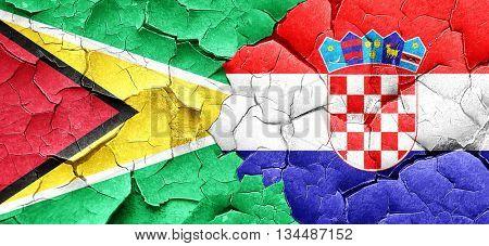 Guyana flag with Croatia flag on a grunge cracked wall