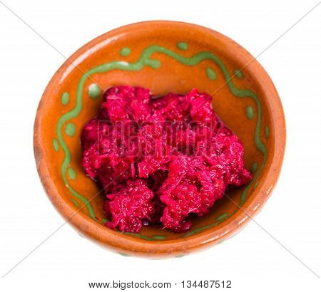 Spicy horseradish sauce on brown clay bowl. Isolated on a white background.