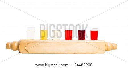 Alcoholic tinctures mix. Six glasses with various fruit tinctures served in national style on wooden rustic board. Isolated on a white background.