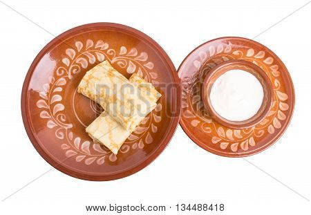 Russian pancakes with chicken fillet. Served with sour cream. Isolated on a white background.