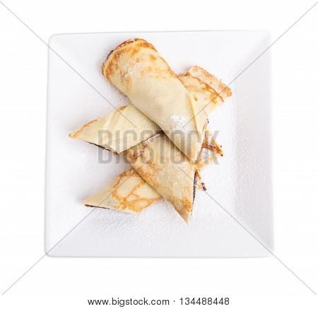 Russian pancakes stuffed with poppy seeds and covered with sugar powder. Isolated on a white background.