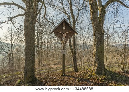 Old weathered wayside cross in the middle of two trees in bavarian forest