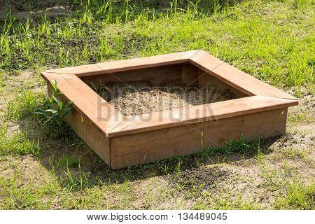 brown children wooden sandbox on the earth
