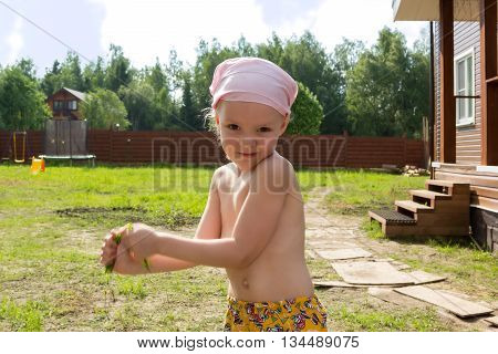 Little Girl Tears A Tuft Of Grass In Hands
