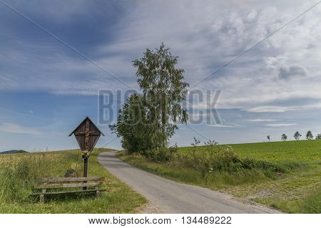 Wayside cross and wooden bench in the bavarian forest