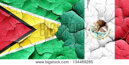 Guyana flag with Mexico flag on a grunge cracked wall
