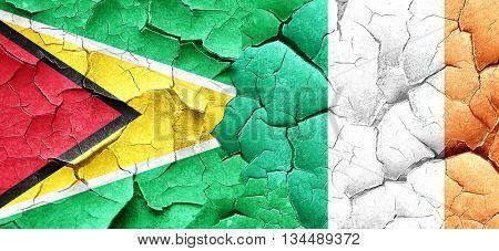 Guyana flag with Ireland flag on a grunge cracked wall