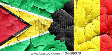 Guyana flag with Belgium flag on a grunge cracked wall