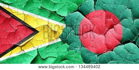 Guyana flag with Bangladesh flag on a grunge cracked wall