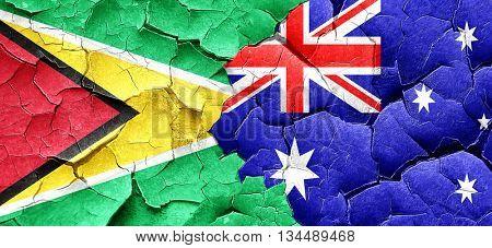 Guyana flag with Australia flag on a grunge cracked wall