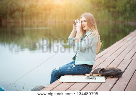 Outdoor summer smiling lifestyle portrait of pretty young woman traveling with camera and making pictures. Young girl tourist in sun glasses making photo