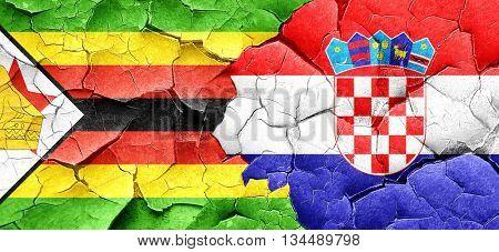 Zimbabwe flag with Croatia flag on a grunge cracked wall