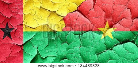 Guinea bissau flag with Burkina Faso flag on a grunge cracked wa