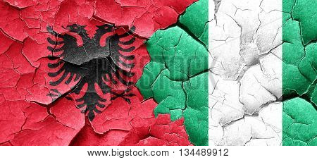 Albania flag with Nigeria flag on a grunge cracked wall