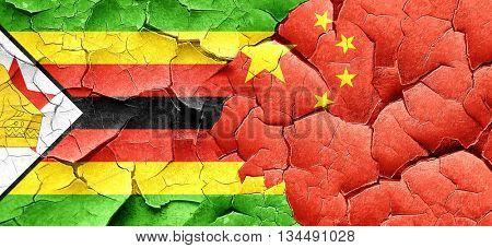 Zimbabwe flag with China flag on a grunge cracked wall