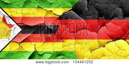 Zimbabwe flag with Germany flag on a grunge cracked wall