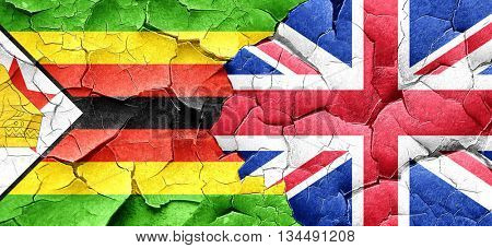 Zimbabwe flag with Great Britain flag on a grunge cracked wall