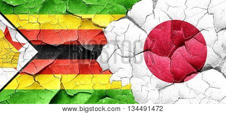 Zimbabwe flag with Japan flag on a grunge cracked wall
