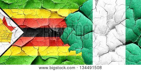 Zimbabwe flag with Nigeria flag on a grunge cracked wall