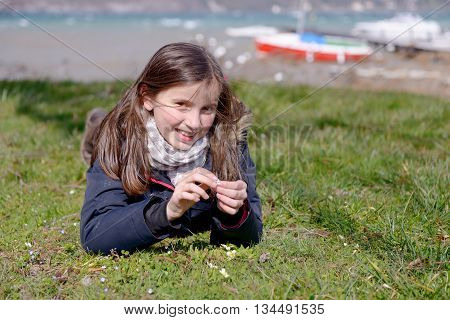 a pretty preteen is lying in the green grass in the spring