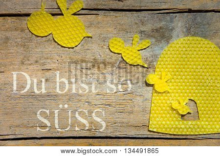 Beeswax, Bees And A Beehive On Wooden Table, German Text, Concept Sweetheart