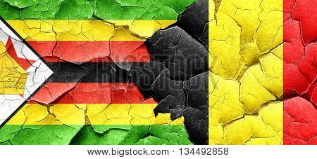 Zimbabwe flag with Belgium flag on a grunge cracked wall