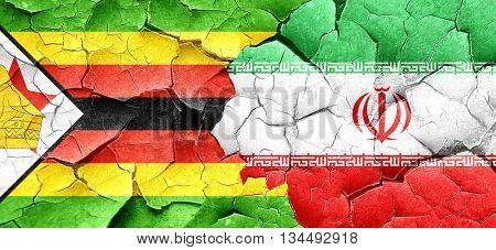 Zimbabwe flag with Iran flag on a grunge cracked wall
