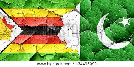 Zimbabwe flag with Pakistan flag on a grunge cracked wall