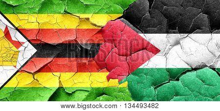 Zimbabwe flag with Palestine flag on a grunge cracked wall