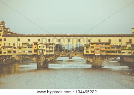 Stylized antique photo. View of the beautiful city Florence with amazing bridge Ponte Vecchio a and Arno river,Tuscany, Italy. Travel destination.