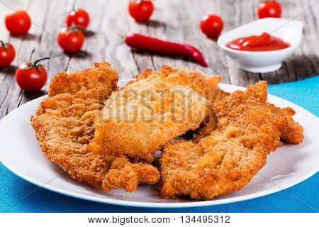 Bread Crumb Coated Fried Chicken breast on a white dish on a table mat with red chili pepper cherry tomatoes and ketchup in gravy boat on wooden background studio lights close-up