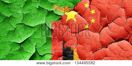 Zambia flag with China flag on a grunge cracked wall