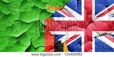 Zambia flag with Great Britain flag on a grunge cracked wall