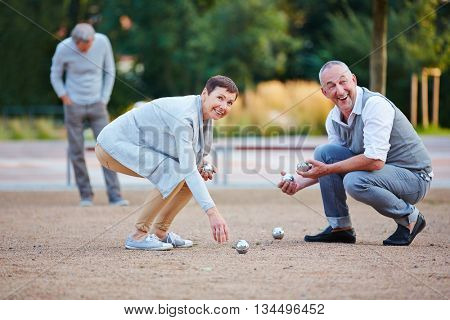 Senior people playing boule lifting up balls from the ground
