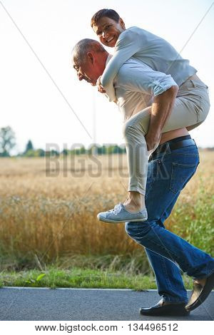Old man giving woman piggyback ride on his back in summer