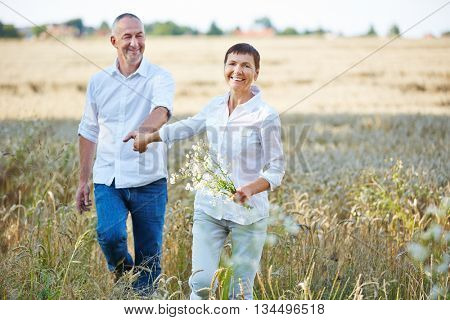 Senior couple with flowers walking in nature in summer