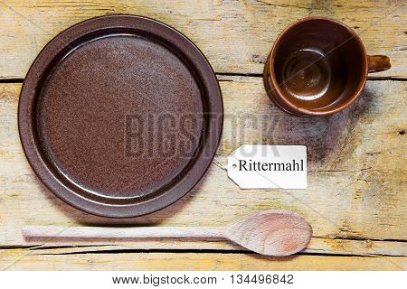 Pottery Dishes And Spoon On Old Wooden Table, Note With German Word, Knight Dinner