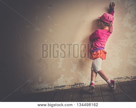 Little four years old girl practicing her salsa dancing moves outside a dilapidated building