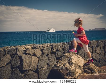 Little four years old girl standing on the seaside promenade and watching passenger ferry sailing away into the sea