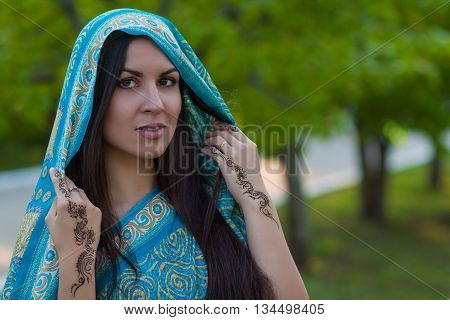 Woman wearing traditional sari with henna tattoo outdoors
