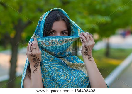 Asian woman hides her face and shows henna tattoo