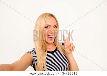 Comic Selfie Of Playful Girl Showing Tongue And Two Fingers