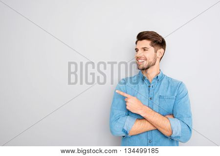 Cheerful Young Man Pointing Away On Gray Background