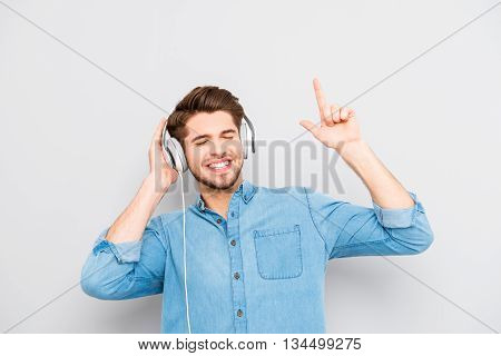 Happy Young Man Listening To Music On Headphones And Dancing