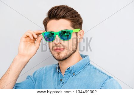 handsome stylish young man holding glasses and smiling