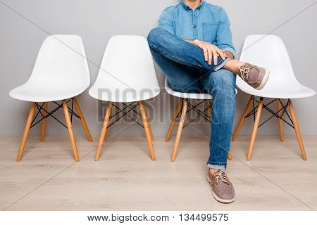 Waiting. Relaxing Young Man Holding Legs And  Sitting On Chair