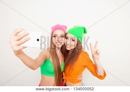 Two Smiling Hipster Girls Shooting On Mobile Phone