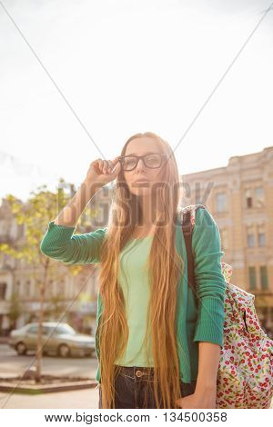 Pretty Young Woman In Glasses With Backpack Walking On The Street