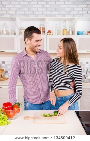 Smilling Couple In Love Cutting Cuumbers In The Kitchen